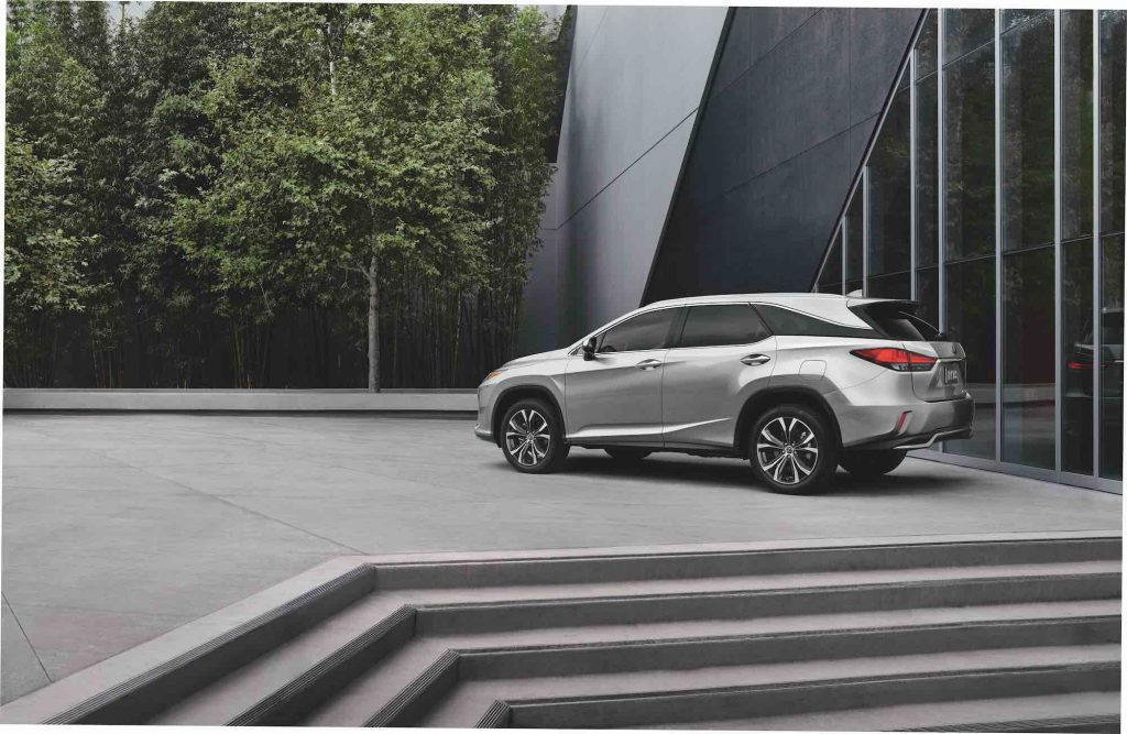 A silver 2021 Lexus RX L midsize luxury SUV parked at the top of some concrete steps next to a modern building and trees