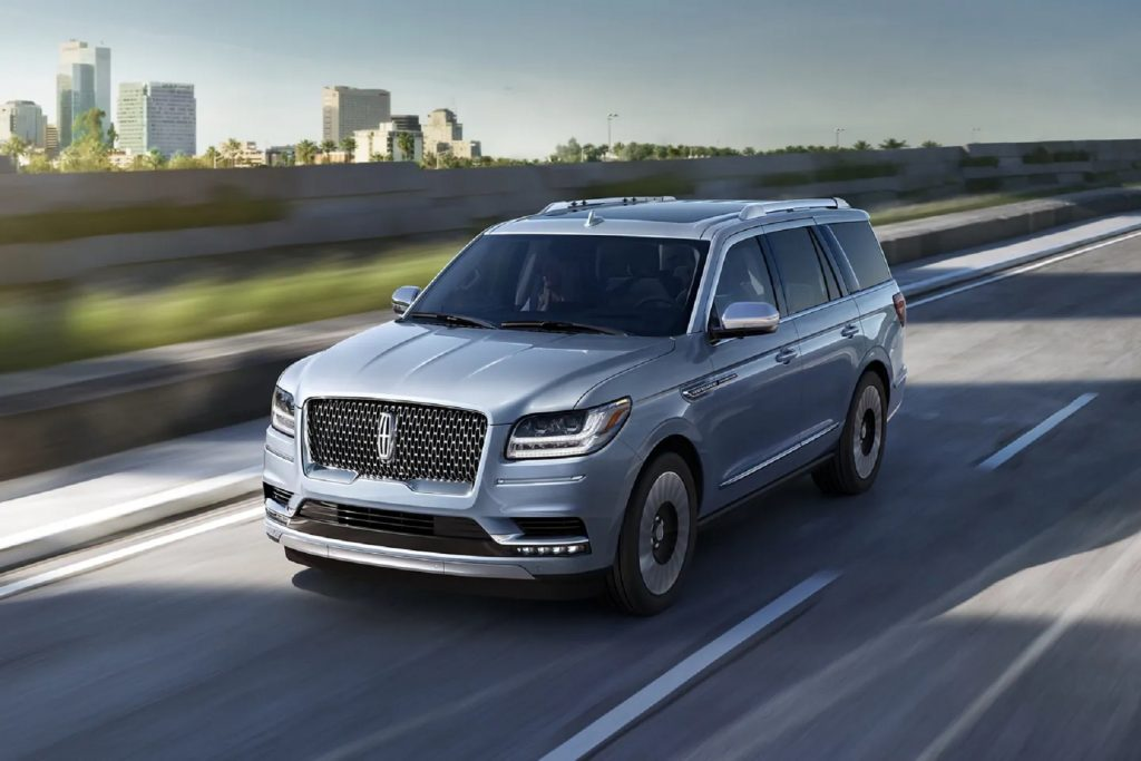 A pale-blue 2021 Lincoln Navigator Black Label SUV driving down the highway by a city