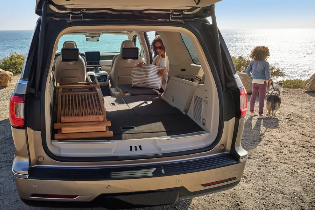 The rear view of the tan-leather interior of a 2021 Lincoln Navigator with its seats folded, loaded with folded wooden chairs by a beach