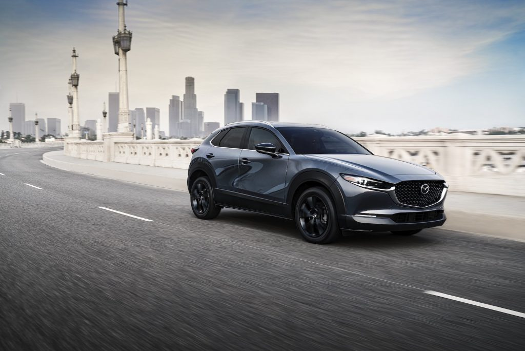 A metallic bluish-gray 2021 Mazda CX-30 2.5 Turbo subcompact crossover SUV travels on a bridge away from a city