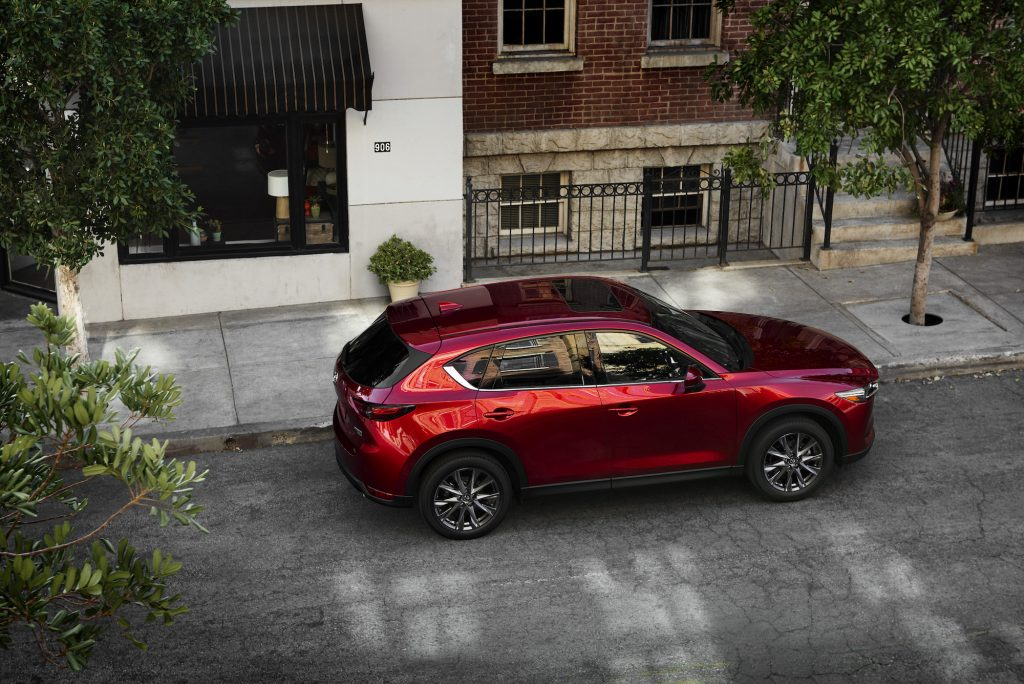 A red 2021 Mazda CX-5 parked on a tree-lined city street