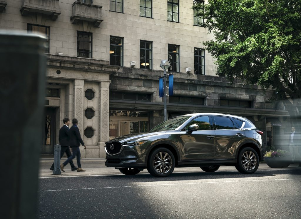 A dark-gray 2021 Mazda CX-5 compact crossover SUV parallel-parked outside a stone office building as two businesspeople walk by
