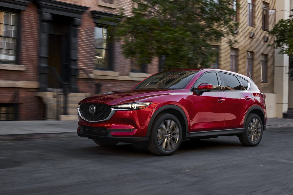A red 2021 Mazda CX-5 driving down a city road with a building and tree in the background