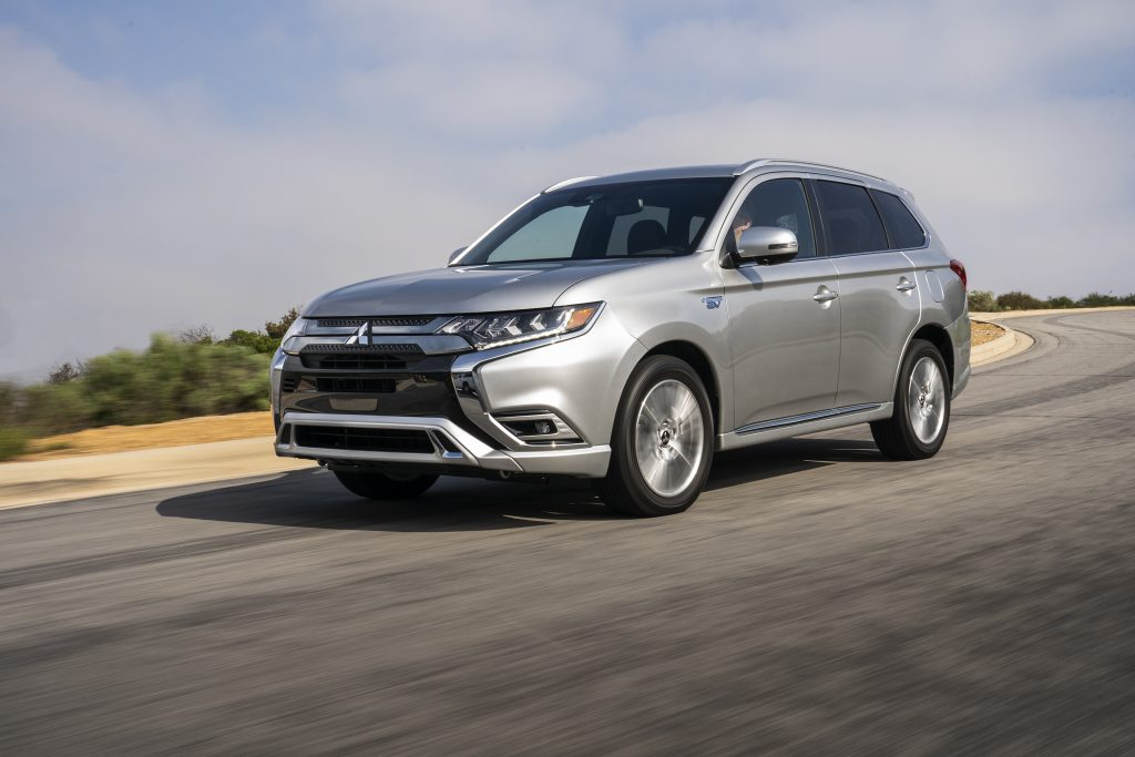 A silver 2021 Mitsubishi Outlander PHEV safely driving down a highway road