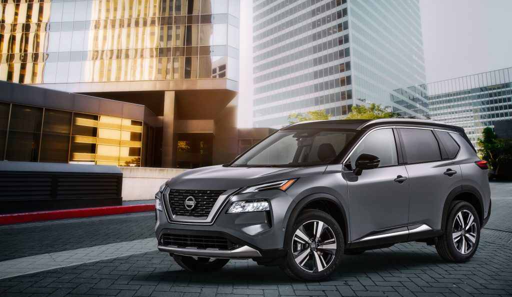 A dark-gray metallic 2021 Nissan Rogue compact crossover SUV parked outside glass skyscrapers