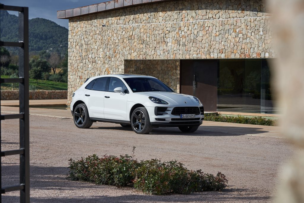 A white 2021 Porsche Macan luxury compact crossover SUV parked outside a stone building with mountains in the background