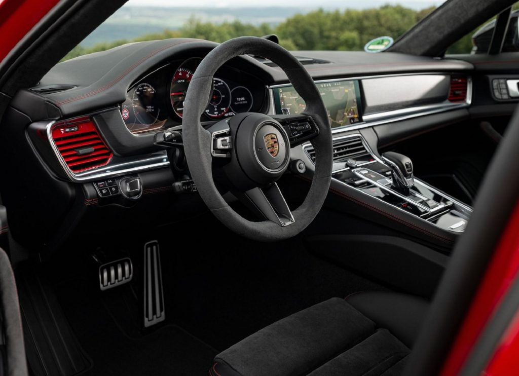The black-suede-trimmed front seats and dashboard of a red 2021 Porsche Panamera GTS
