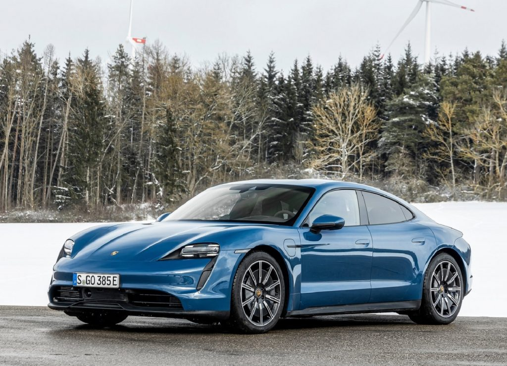 A blue 2021 Porsche Taycan parked by a snowy forest