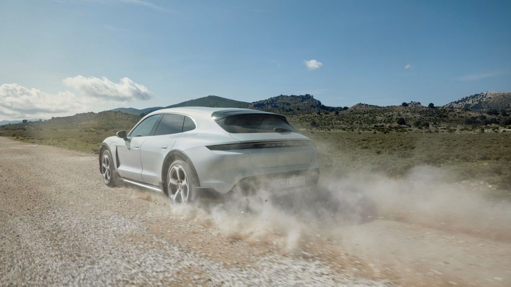 The rear 3/4 view of a white 2021 Porsche Taycan 4S Cross Turismo accelerating down a gravel road