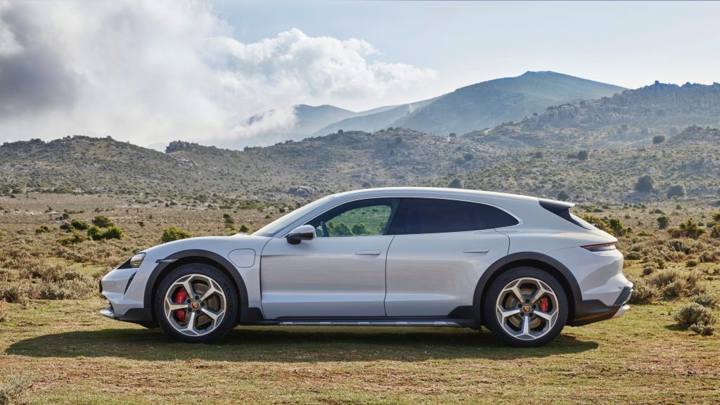 The side view of a white 2021 Porsche Taycan 4S Cross Turismo on a grassy mountain moor