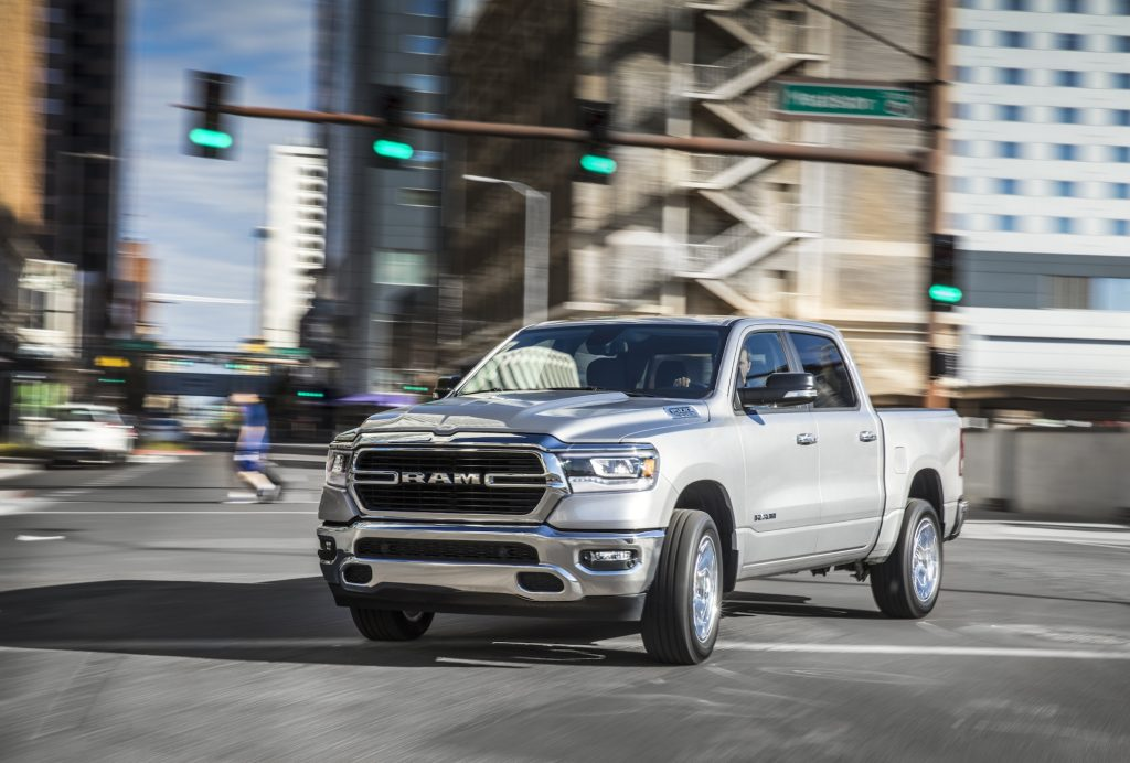 A silver 2021 Ram 1500 Big Horn four-door full-size pickup truck turning in a city intersection