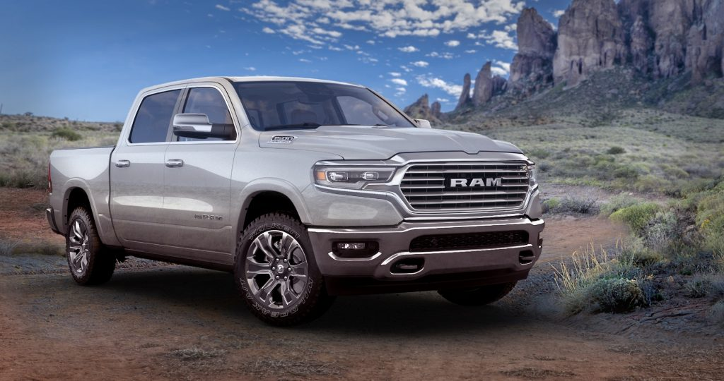 A silver 2021 Ram 1500 Limited Longhorn 10th Anniversary Edition pickup truck parked in a desert is now one of the most discounted new cars