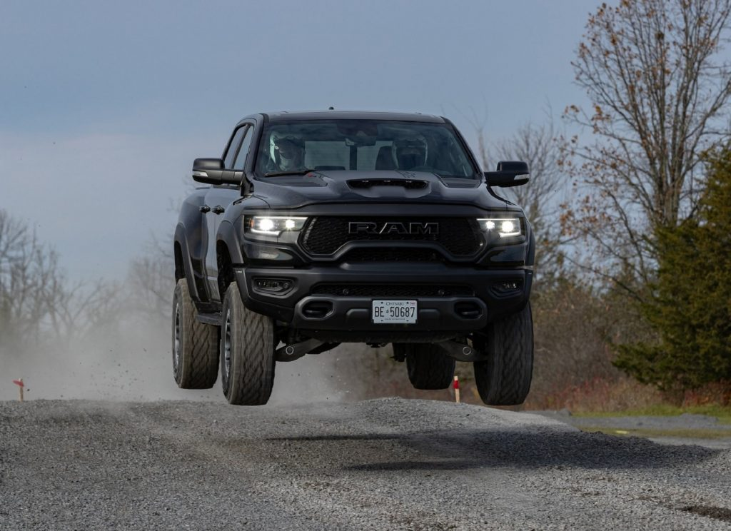 A black 2021 Ram 1500 TRX jumping through the air above a gravel road