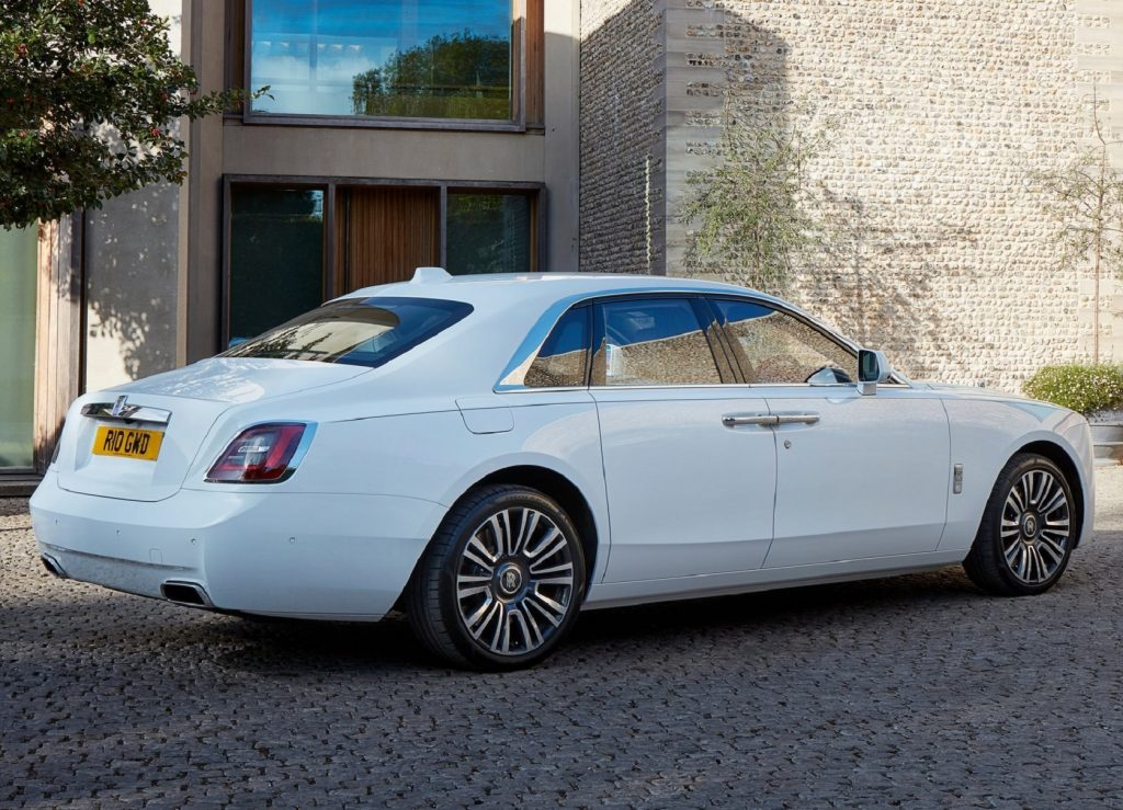 The rear 3/4 view of a white 2021 Rolls-Royce Ghost by a stone building