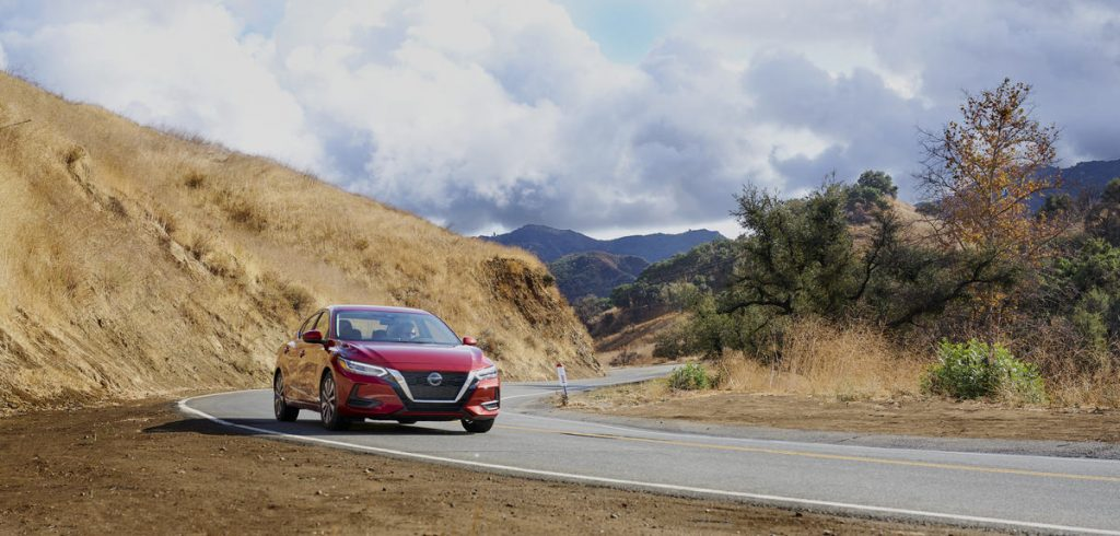 A red 2021 Nissan Sentra driving down a windy road