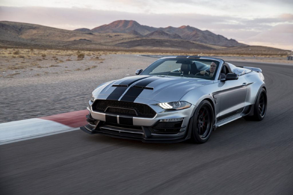 A silver-with-black-stripes 2021 Shelby Super Snake Speedster drives on a desert racetrack