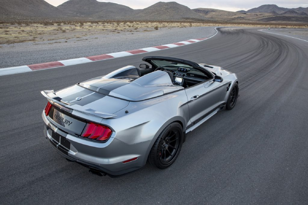An overhead rear 3/4 view of a silver-with-black-stripes 2021 Shelby Super Snake Speedster on a desert racetrack