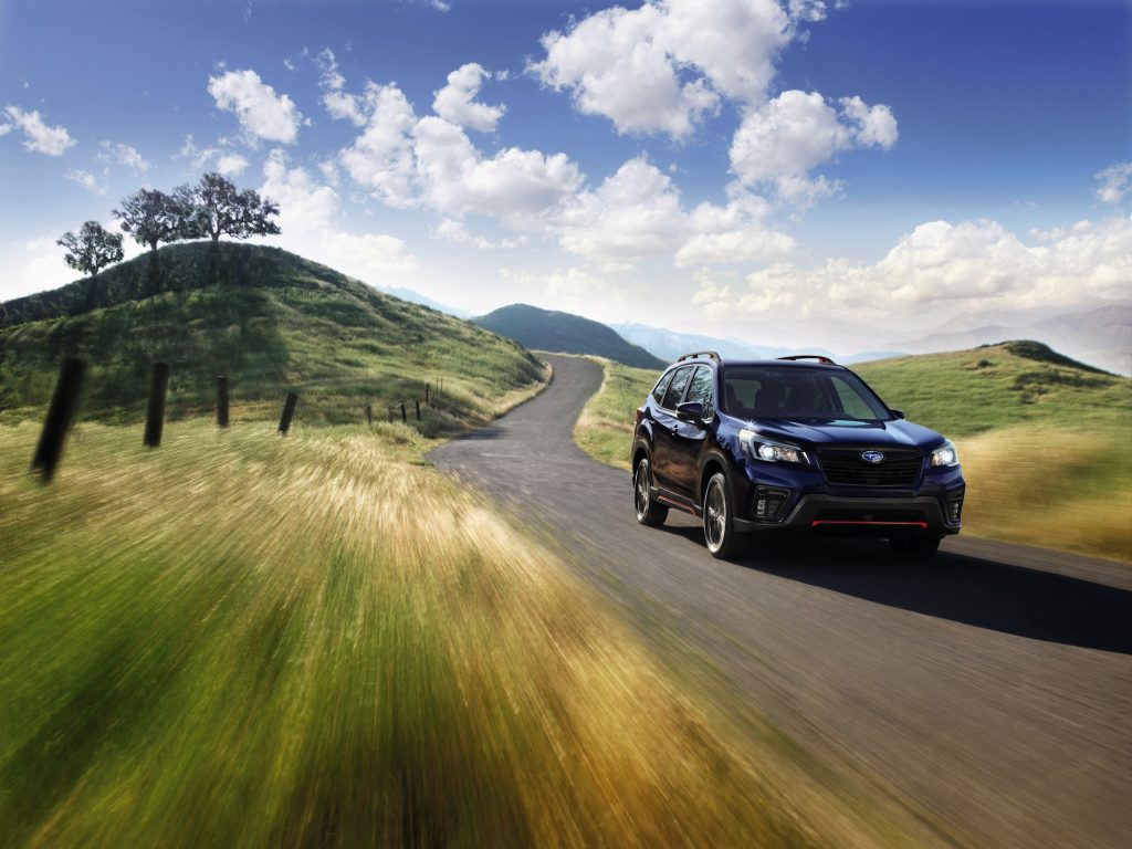 A dark-blue 2021 Subaru Forester all-wheel-drive compact crossover SUV travels on a winding road through green rolling hills on a sunny day