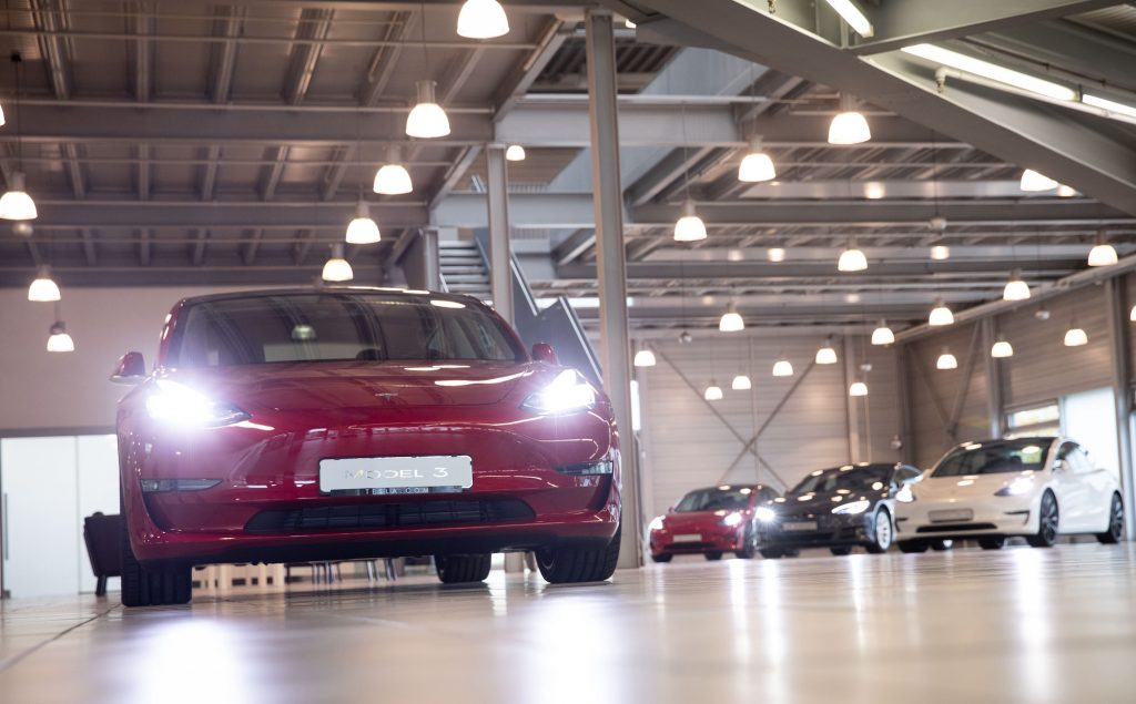 A red Tesla Model 3 EV and other models at the Tesla Service Center in Hamburg, Germany, on October 21, 2020