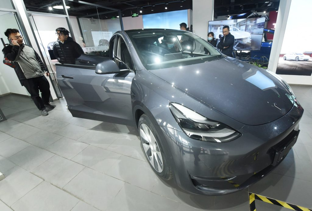 Customers look at the first Tesla Model Y electric SUV arriving at a Tesla store in Hangzhou, Zhejiang Province, China, on January. 4, 2021