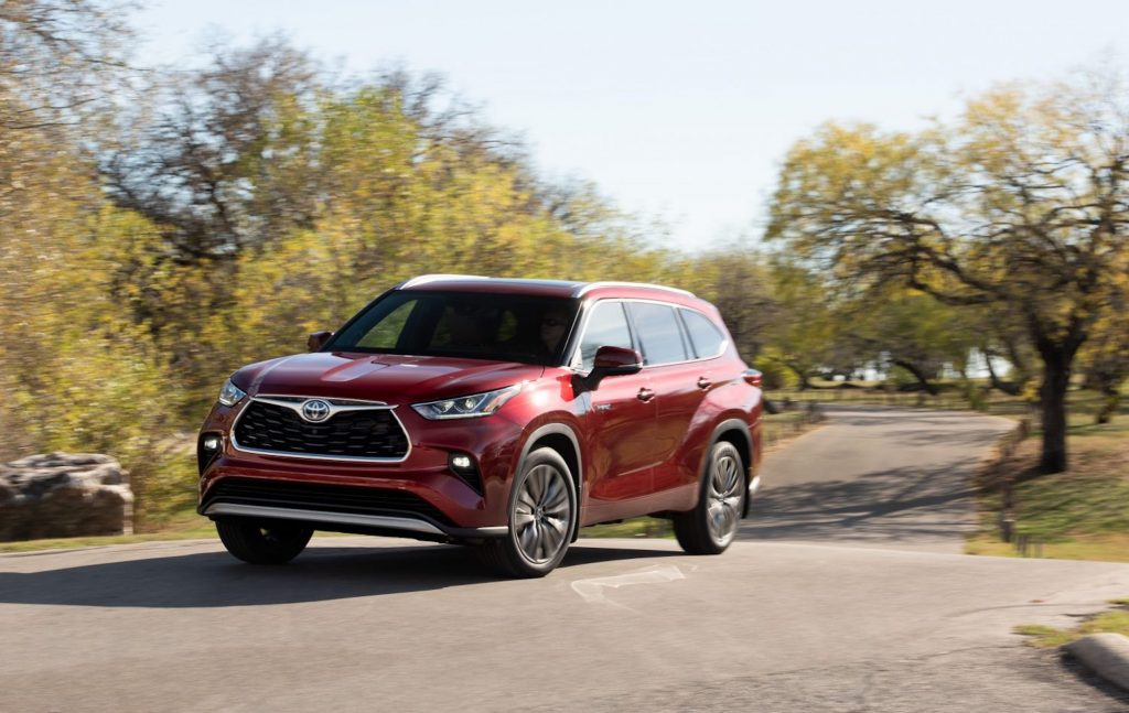 A metallic-red 2021 Toyota Highlander Hybrid midsize crossover SUV traveling on a road in a park with green grass and trees