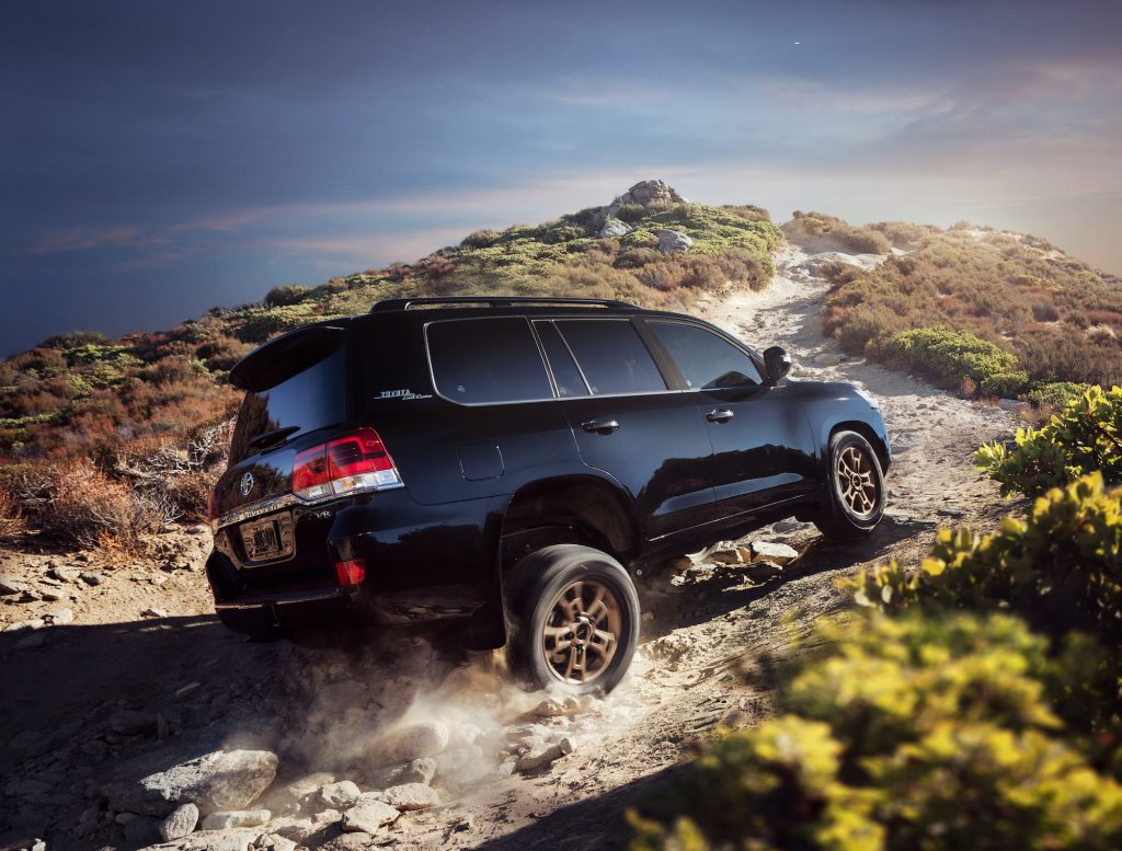 A black 2021 Toyota Land Cruiser four-wheel-drive full-size SUV travels on a dusty, rocky path up a hill