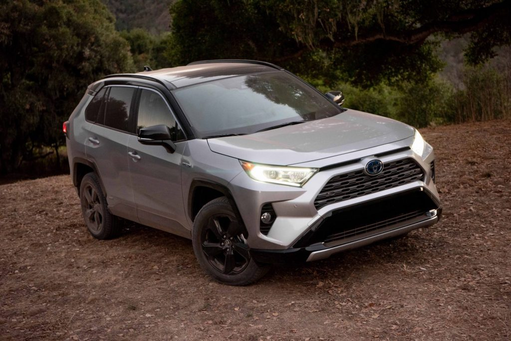 A silver 2021 Toyota RAV4 XSE Hybrid compact crossover SUV parked on the dirt in front of shrubs and trees