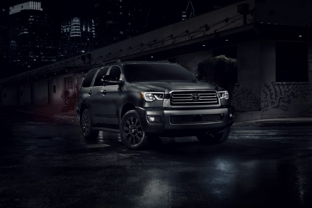 A dark-gray 2021 Toyota Sequoia Nightshade large SUV on a city street at night