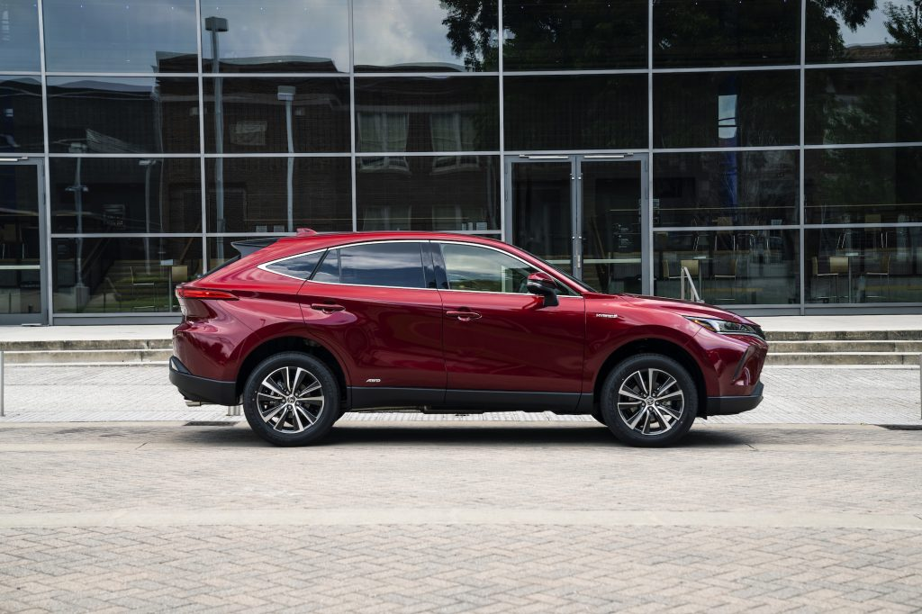 A red 2021 Toyota Venza LE midsize crossover SUV parked on brick pavers next to a sidewalk outside a glass building