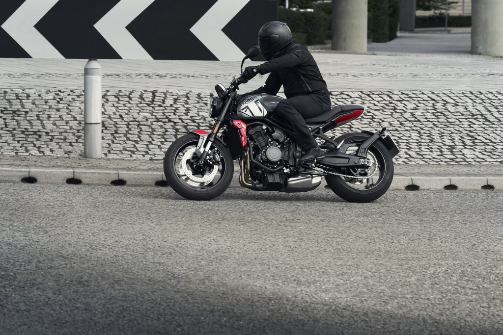 A black-clad rider takes the gray-and-black 2021 Triumph Trident 660 around a street corner