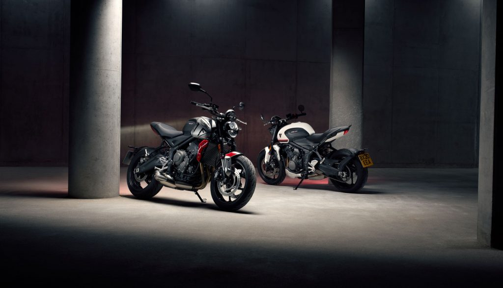 A gray and a white 2021 Triumph Trident 660 with accessories parked in a dark concrete room