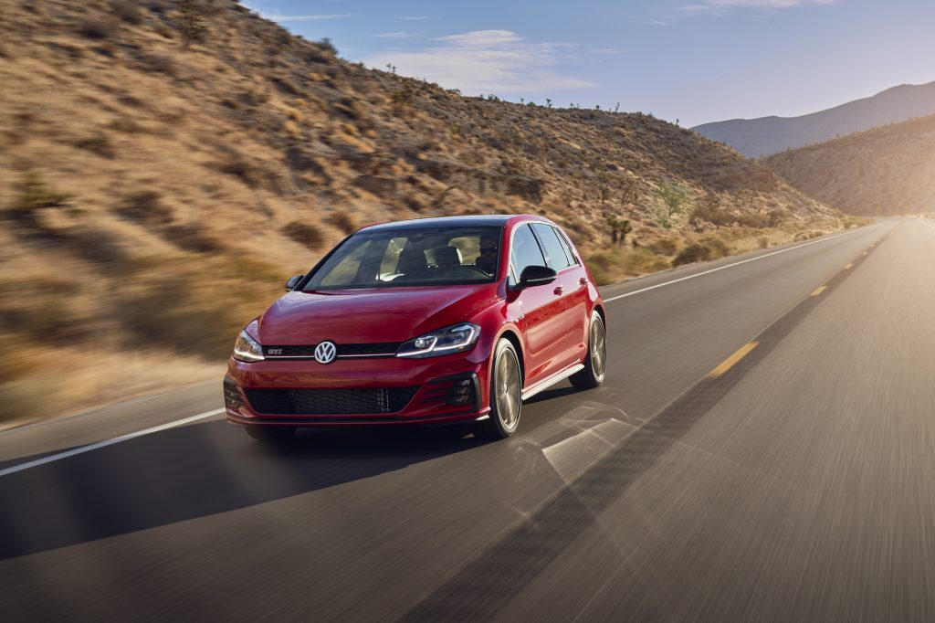 A red 2021 Volkswagen GTI four-door hatchback traveling on a two-lane highway through arid mountains on a sunny day