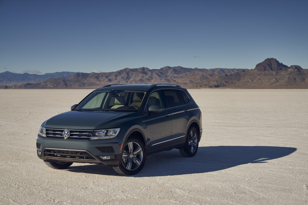 A dark-gray 2021 Volkswagen Tiguan compact crossover SUV parked in a desert with mountains in the background