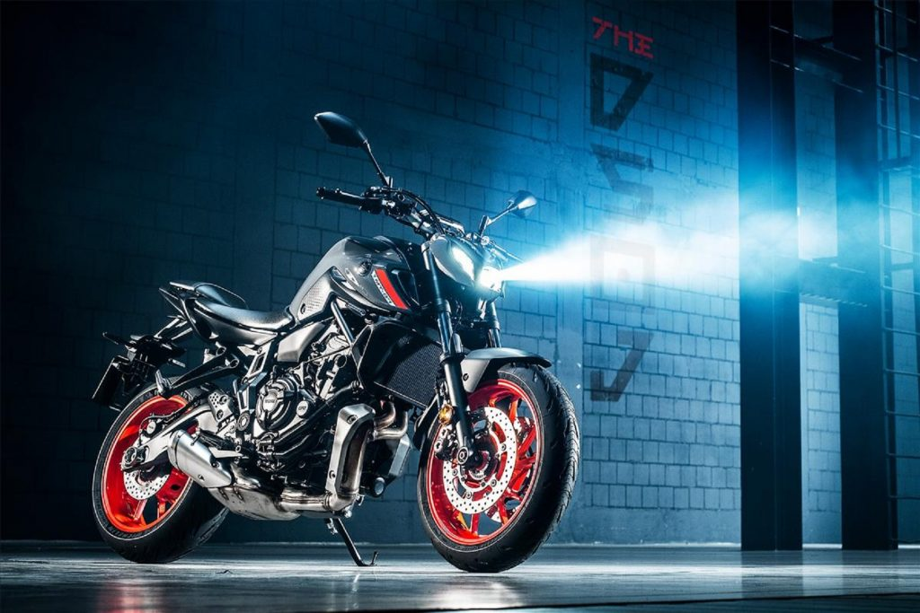 A gray 2021 Yamaha MT-07 with its headlight on in a concrete garage