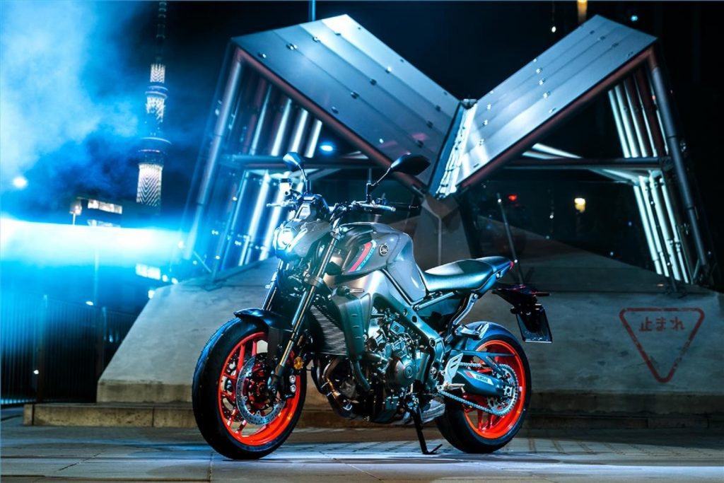 A gray-and-black-with-orange-wheels 2021 Yamaha MT-09 in front of a building at night