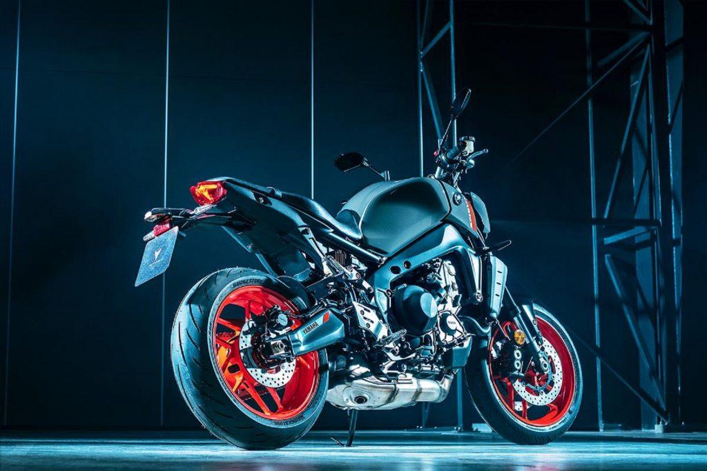 A low-angle rear 3/4 view of a gray-and-black-with-orange-wheels 2021 Yamaha MT-09 in a dark room