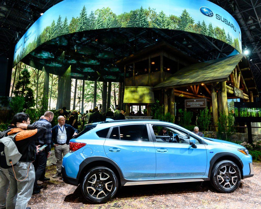 A blue 2021 Subaru Crosstrek Hybrid on a nature display at the New York Auto Show