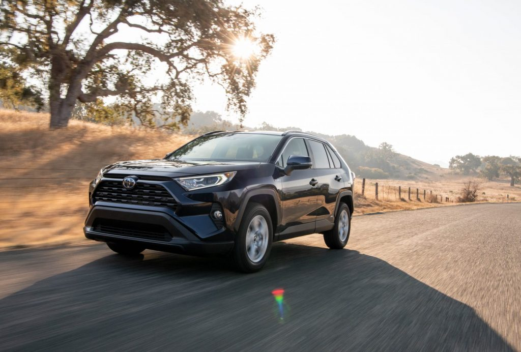 A 2021 Toyota RAV4 Hybrid shown in blue driving down the road