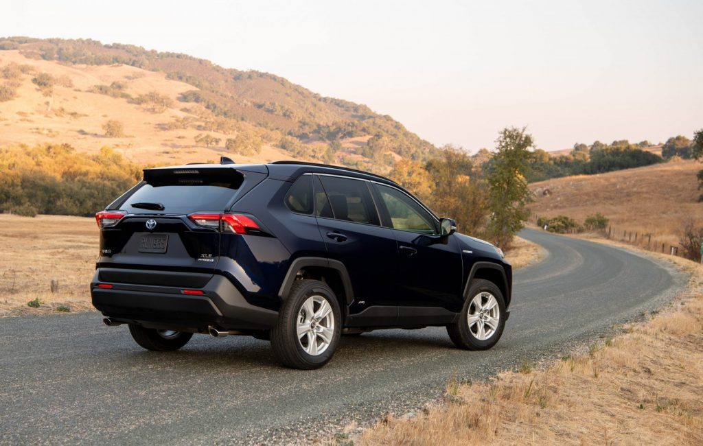 2021 Toyota RAV4 Hybrid in blue shot from the rear on a country road.