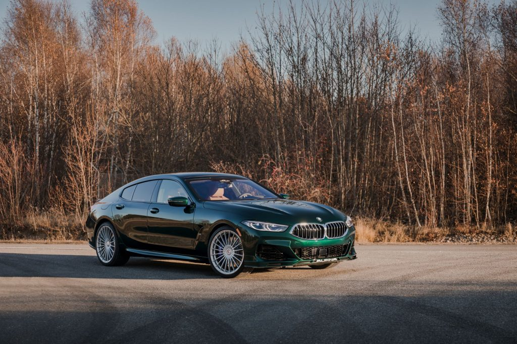 A dark-green 2022 BMW Alpina B8 Gran Coupe parked by a winter-time forest