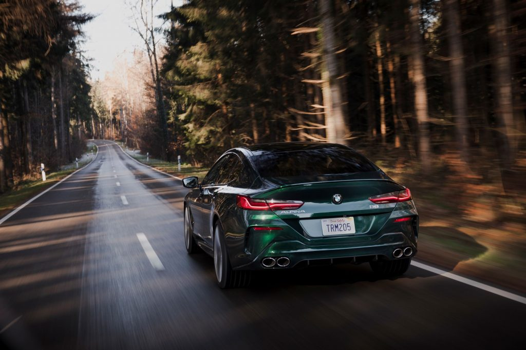 The rear view of a dark-green 2022 BMW Alpina B8 Gran Coupe driving down a road through a pine forest