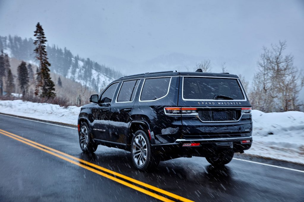 The rear 3/4 view of a dark-blue 2022 Jeep Grand Wagoneer Series III driving on a mountain road as snow falls