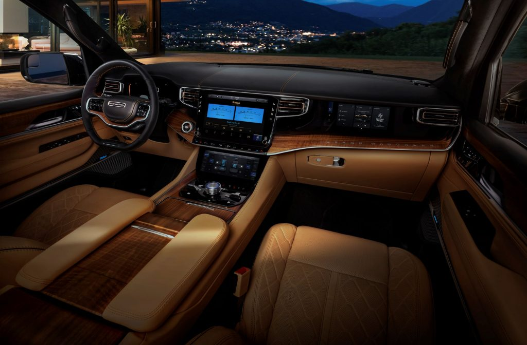 The tan-leather front seats and walnut-lined dashboard of a 2022 Jeep Grand Wagoneer