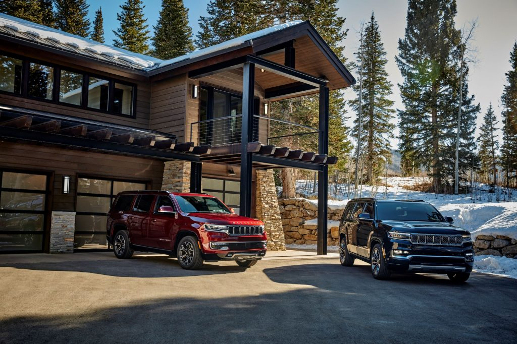 A red 2022 Jeep Wagoneer Series II next to a dark-blue 2022 Grand Wagoneer Series III by a wooden forest cabin