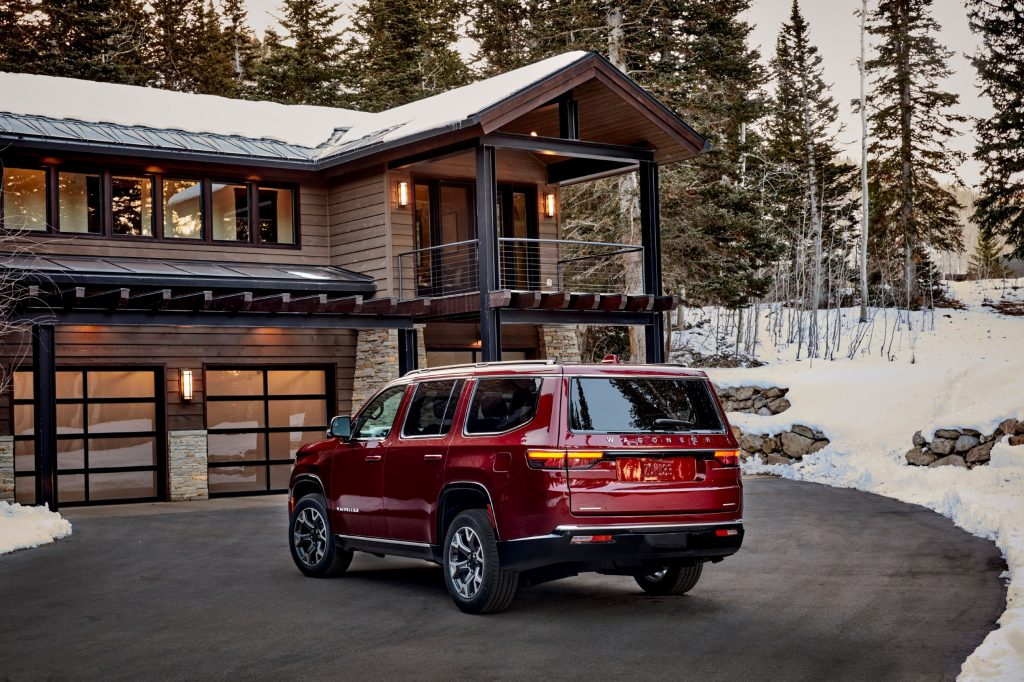 The rear 3/4 view of a red 2022 Jeep Wagoneer Series II next to a wooden cabin in a snowy forest