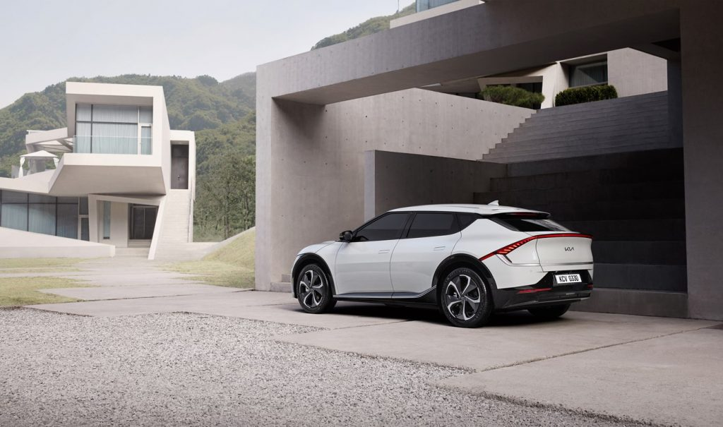 A White 2022 Kia EV6 parked in front of a modern home
