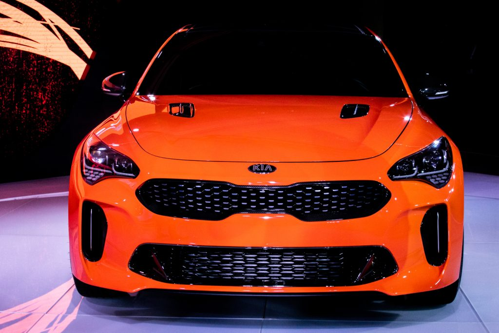 An orange Kia Stinger on display at a car event