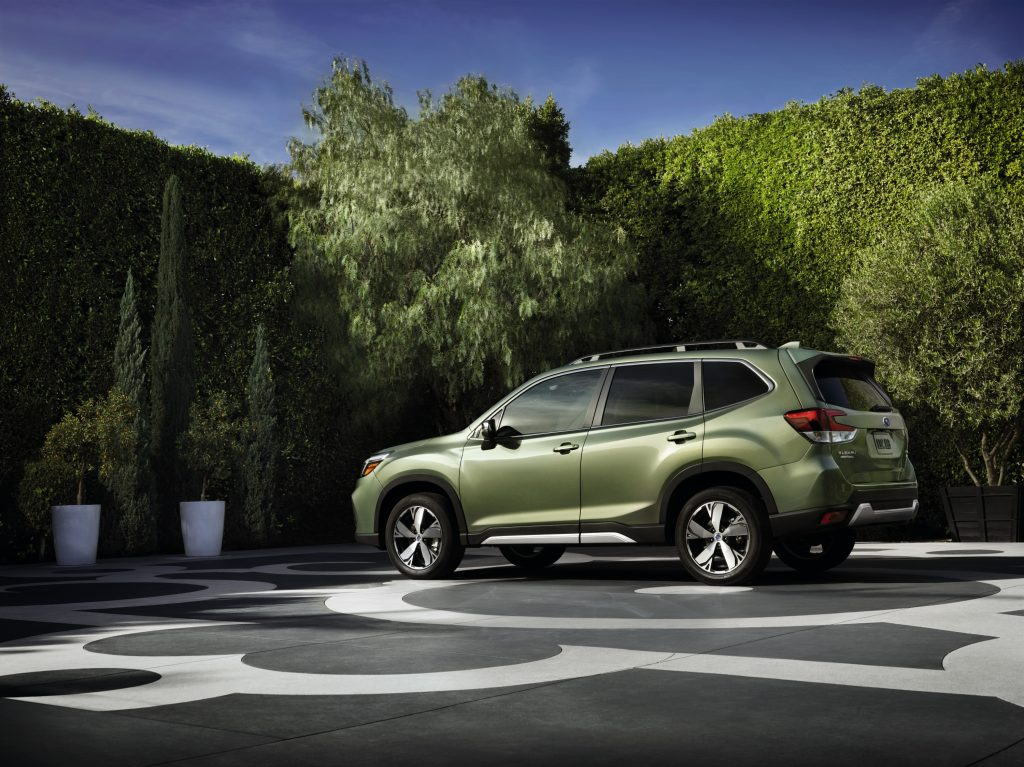A green 2020-2021 Subaru Forester on display in a parking lot with green bushes in the background