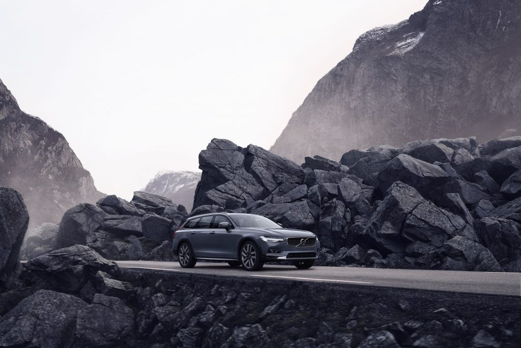 grey Volvo driving through the mountains