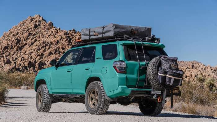 rendering of a teal Toyota 4runner trd pro in the desert with a roof tent